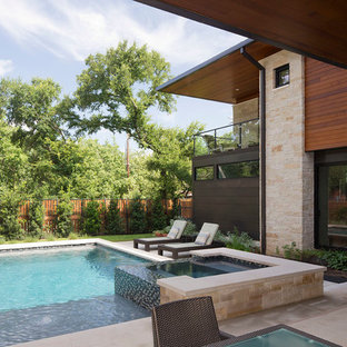 Trendy backyard stone and rectangular hot tub photo in Austin