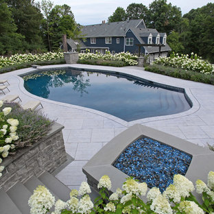 Large contemporary side yard custom-shaped lap pool in New York with tile.