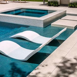 Foto de piscinas y jacuzzis infinitos, actuales, pequeños, rectangulares, en patio trasero, con suelo de baldosas