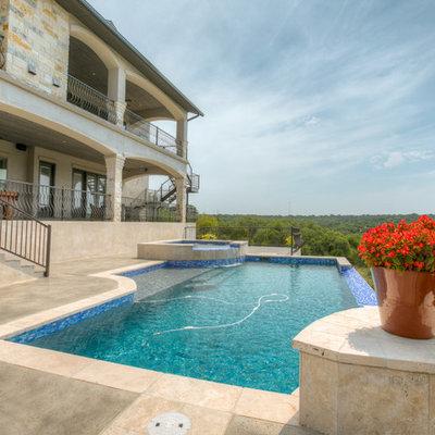Large tuscan backyard concrete and rectangular infinity hot tub photo in Austin