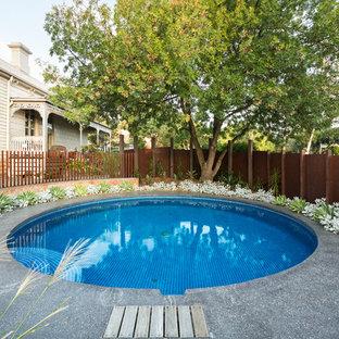 Modelo de piscina moderna, de tamaño medio, redondeada, en patio lateral, con gravilla