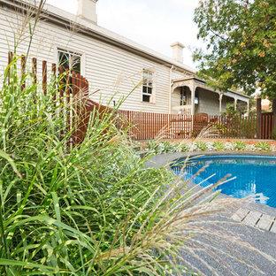 Ejemplo de piscina moderna, de tamaño medio, redondeada, en patio lateral, con gravilla