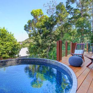 Ejemplo de piscina elevada, contemporánea, pequeña, redondeada, en patio trasero, con entablado