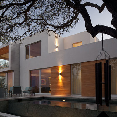 Example of a large trendy backyard concrete paver and rectangular infinity pool design in Austin
