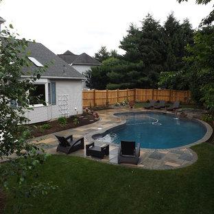 Imagen de piscinas y jacuzzis tradicionales, grandes, tipo riñón, en patio trasero, con adoquines de hormigón