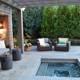 Shabby-chic style pool in Other with a hot tub and natural stone pavers.