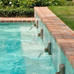 Foto de piscina con fuente alargada, tradicional, grande, rectangular, en patio trasero, con adoquines de ladrillo
