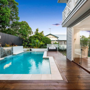 Inspiration for a transitional backyard rectangular natural pool in Brisbane with a water feature and decking.