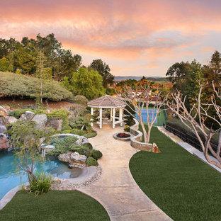 Esempio di una grande piscina chic personalizzata dietro casa con pavimentazioni in cemento e una vasca idromassaggio