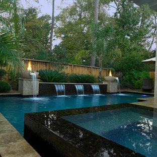 Imagen de piscina con fuente alargada, actual, grande, en forma de L, en patio trasero, con suelo de baldosas