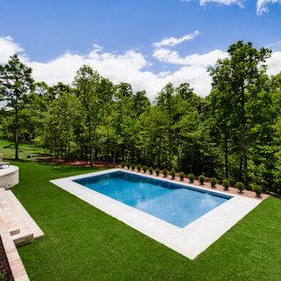 Exemple d'une grand piscine arrière chic rectangle avec un aménagement paysager autour d'une piscine et une dalle de béton.