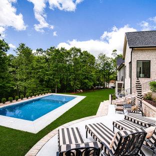 Foto de piscina tradicional renovada, grande, rectangular, en patio trasero, con losas de hormigón