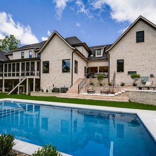 Modelo de piscina clásica renovada, grande, rectangular, en patio trasero, con losas de hormigón