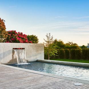 Foto de piscina con fuente alargada, vintage, grande, rectangular, en patio trasero, con entablado