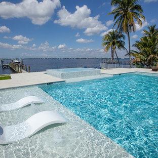 Foto de piscinas y jacuzzis infinitos, modernos, de tamaño medio, rectangulares, en patio trasero, con suelo de baldosas