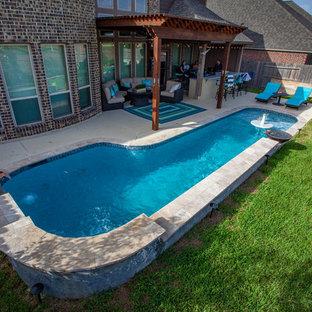 Imagen de piscina con fuente natural, exótica, pequeña, en forma de L, en patio trasero, con suelo de baldosas
