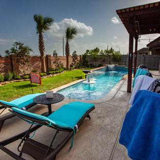 Foto de piscina con fuente natural, tropical, pequeña, en forma de L, en patio trasero, con suelo de baldosas