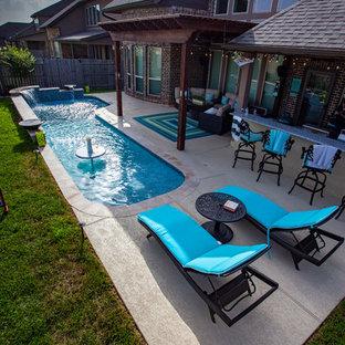 Modelo de piscina con fuente natural, exótica, pequeña, en forma de L, en patio trasero, con suelo de baldosas