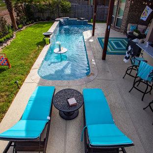 Diseño de piscina con fuente natural, tropical, pequeña, en forma de L, en patio trasero, con suelo de baldosas