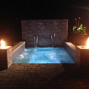 Aménagement d'une petit piscine arrière contemporaine rectangle avec des pavés en brique et un bain bouillonnant.