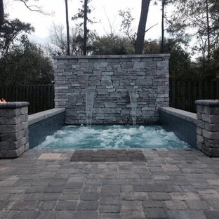 Design ideas for a small country backyard rectangular pool in Jacksonville with brick pavers and a hot tub.
