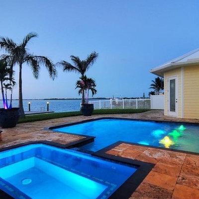 Mid-sized island style backyard stone and rectangular lap hot tub photo in Orlando