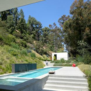 Imagen de casa de la piscina y piscina alargada, minimalista, pequeña, rectangular, en patio trasero, con losas de hormigón