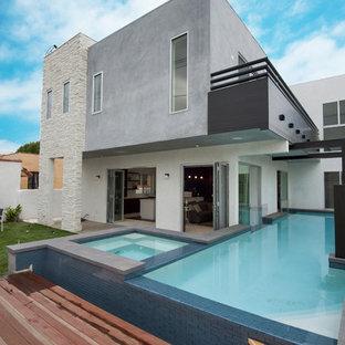 Modelo de piscinas y jacuzzis elevados, actuales, de tamaño medio, en forma de L, en patio trasero, con entablado