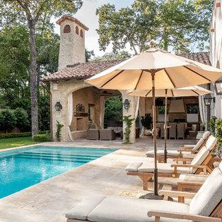 Mittelgroßes Mediterranes Sportbecken hinter dem Haus in rechteckiger Form mit Natursteinplatten in Houston
