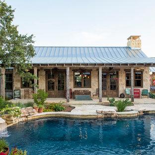 Ejemplo de casa de la piscina y piscina rural, de tamaño medio, a medida, en patio trasero, con adoquines de piedra natural
