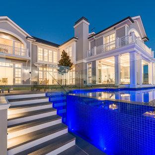 Diseño de piscina elevada, contemporánea, en forma de L, en patio trasero