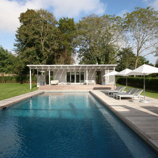 Pool house - large modern backyard rectangular pool house idea in New York with decking