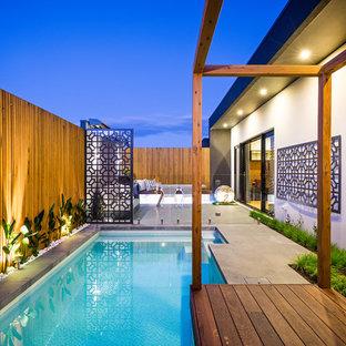 Foto de piscina alargada, contemporánea, pequeña, a medida, en patio trasero, con entablado