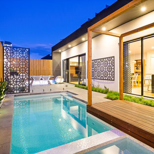 Inspiration for a contemporary side yard custom-shaped lap pool in Melbourne with a hot tub and concrete pavers.