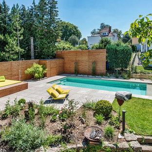 Modelo de piscina con fuente alargada, actual, de tamaño medio, rectangular, en patio trasero, con adoquines de piedra natural