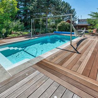 Ejemplo de piscina con fuente alargada, actual, de tamaño medio, rectangular, en patio trasero, con entablado