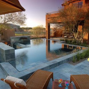 Diseño de piscina con fuente infinita, moderna, grande, rectangular, en patio trasero, con suelo de hormigón estampado