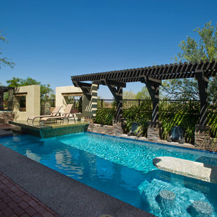 Large minimalist backyard brick and custom-shaped infinity pool fountain photo in Phoenix