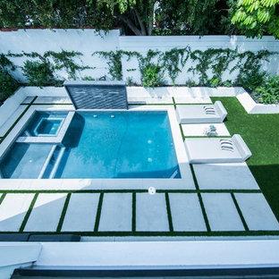 Ejemplo de piscinas y jacuzzis elevados, de estilo de casa de campo, de tamaño medio, en forma de L, en patio trasero, con adoquines de hormigón