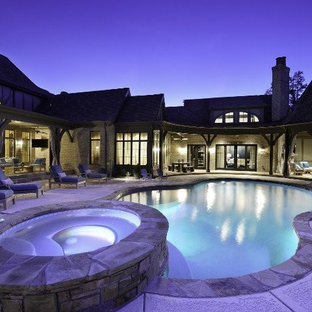 Imagen de piscinas y jacuzzis clásicos, de tamaño medio, tipo riñón, en patio trasero, con losas de hormigón
