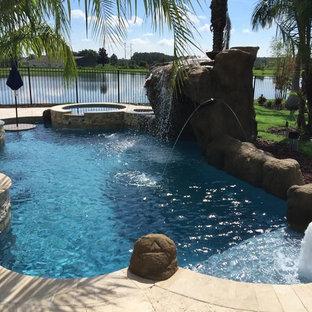 Diseño de piscinas y jacuzzis alargados, tropicales, de tamaño medio, a medida, en patio trasero, con adoquines de piedra natural