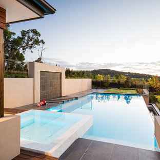 Hot tub - large contemporary rectangular and tile infinity hot tub idea in Melbourne