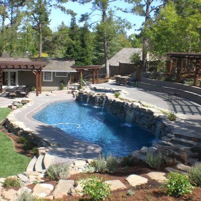 Mid-sized mountain style backyard stone and custom-shaped lap pool fountain photo in San Francisco