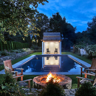 Country rectangular pool in New York with a pool house.