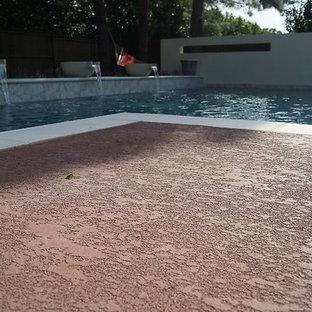 Diseño de piscina con fuente natural, moderna, grande, a medida, en patio trasero, con granito descompuesto