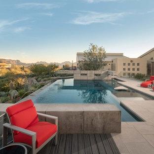 Foto de piscina con fuente infinita, actual, grande, a medida, en patio trasero, con suelo de baldosas