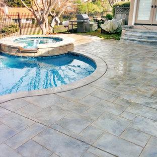 Modelo de piscina natural, de estilo americano, grande, a medida, en patio trasero, con suelo de hormigón estampado