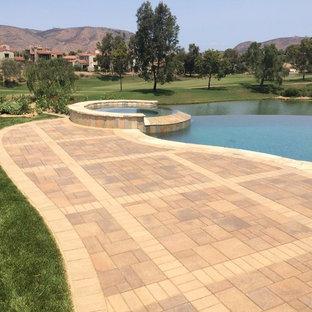 Ejemplo de piscina con fuente alargada, clásica, grande, a medida, en patio trasero, con adoquines de hormigón