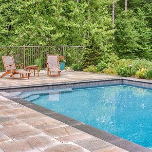 Modelo de piscina infinita, clásica, de tamaño medio, rectangular, en patio lateral, con adoquines de piedra natural