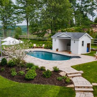 На фото: с высоким бюджетом бассейны среднего размера, произвольной формы на заднем дворе в стиле рустика с домиком у бассейна и мощением тротуарной плиткой